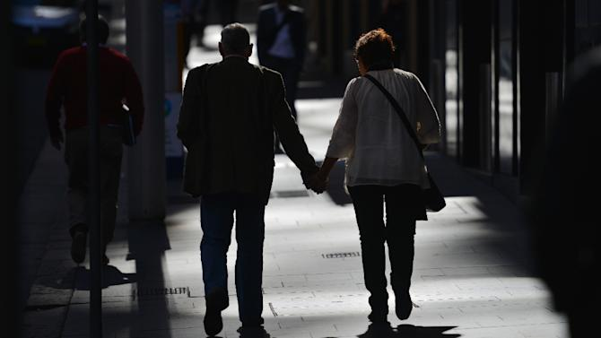 A couple walk hand-in-hand on a street in the Central Business District of Sydney on May 13, 2015