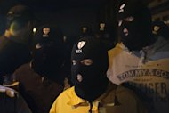 Members of the English Defence League (EDL) wear balaclavas as they gather outside a pub in Woolwich in London on May 22, 2013 after two men wielding knives butchered and beheaded a man believed to be a soldier in a busy London street, before delivering an Islamist tirade to passers-by