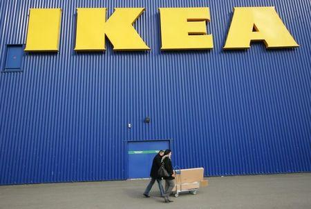 People push a shopping cart past a warehouse of the Swedish furniture maker IKEA in Bordeaux