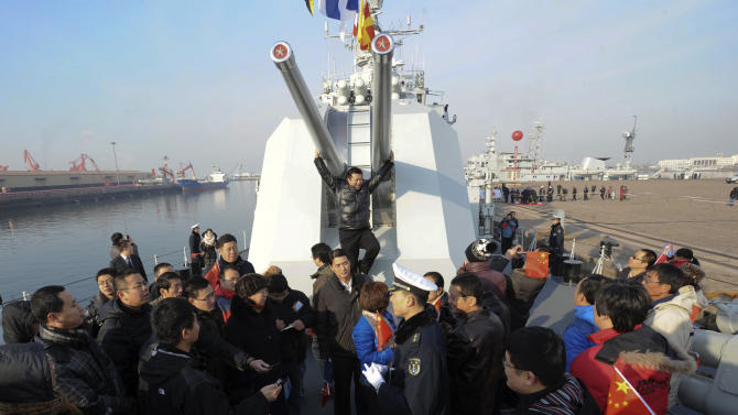 In this Wednesday Dec. 26, 2012, a man, center in back, poses for a photo while others visit Chinese navy's missile destroyer Qingdao on the destroyer's public open day in Qingdao, in eastern China's Shandong province. (AP Photo)  CHINA OUT