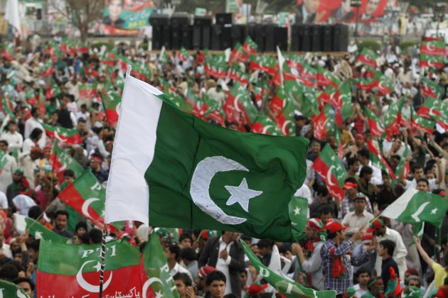 Supporters of the political party PTI wave national and party flags during a rally in Lahore