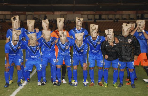 Players of Celaya soccer team pose with brown paper bags over their heads in protest at unpaid wages in Celaya