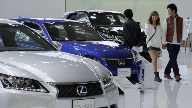 A couple walk by Lexus models displayed at a Toyota Motor Corp. showroom in Tokyo Monday, Nov. 5, 2012. Toyota's quarterly profit tripled, driven by a recovery from natural disasters, and the company raised its full-year earnings forecast despite a sales slump in China. (AP Photo/Koji Sasahara)