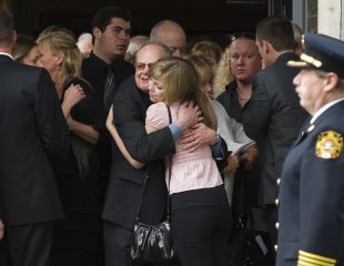 Rolly Fox embraces a granddaughter outside the funeral for his wife Betty.