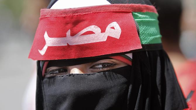 """A veiled Egyptian woman wears a head band in Arabic that reads,""""Egypt,"""" during a protest in Tahrir Square, the focal point of Egyptian uprising, to support judicial independence in Cairo, Egypt, Friday, April 26, 2013. Egypt's Islamist-led parliament on Wednesday pushed ahead with a law that could force into retirement many of the nation's most senior judges, despite an uproar by the judiciary over fears the president's allies want to control the courts. (AP Photo/Amr Nabil)"""