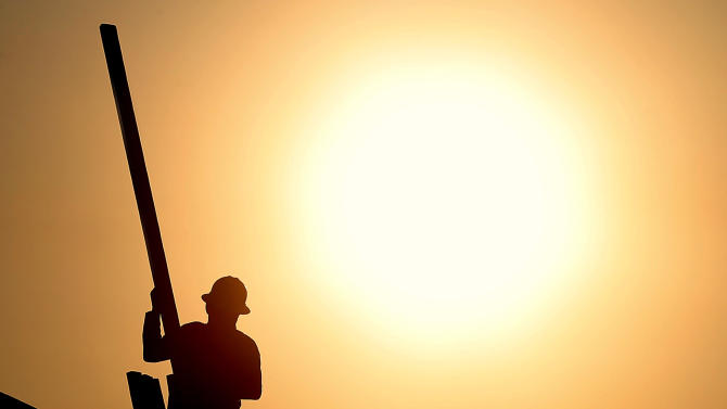 In this Thursday, June 27, 2013, photo, a construction worker is shown atop a roof at sunrise to beat daytime high temperatures in Queen Creek, Ariz. The Commerce Department releases housing starts for June on Tuesday, July 16, 2013. (AP Photo/Matt York)