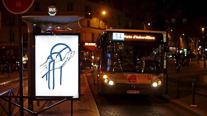 "A poster by street artist Paul Insect as part of the ""Brandalism"" project is displayed at a bus stop in Paris"