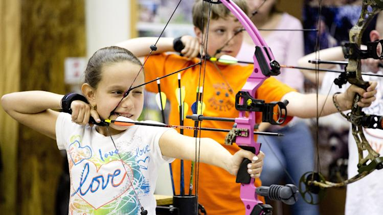 "In this April 13, 2012 photo, Ashley Donzella, of Fair Lawn, N.J., participates in the youth archery league at Targeteers Archery in Saddle Brook, N.J.  In schools and backyards, for their birthdays and out with their dads, kids are gaga for archery a month after the release of ""The Hunger Games."" Archery ranges around the country have enjoyed a steady uptick among kids of both sexes in the movie's lead-up, though 16-year-old heroine Katniss Everdeen, the archery ace seems to resonate with girls more than boys. (AP Photo/Charles Sykes)"