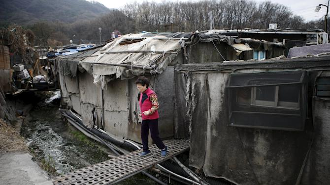 A woman crosses a makeshift bridge at Guryong village in Seoul