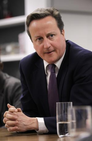 FILE - In this Wednesday, April 4, 2012 file photo British Prime Minister David Cameron meets with social entrepreneurs at the Brigade as part of his launch of Big Society Capital, London. (AP Photo/Sang Tan, Pool, File)