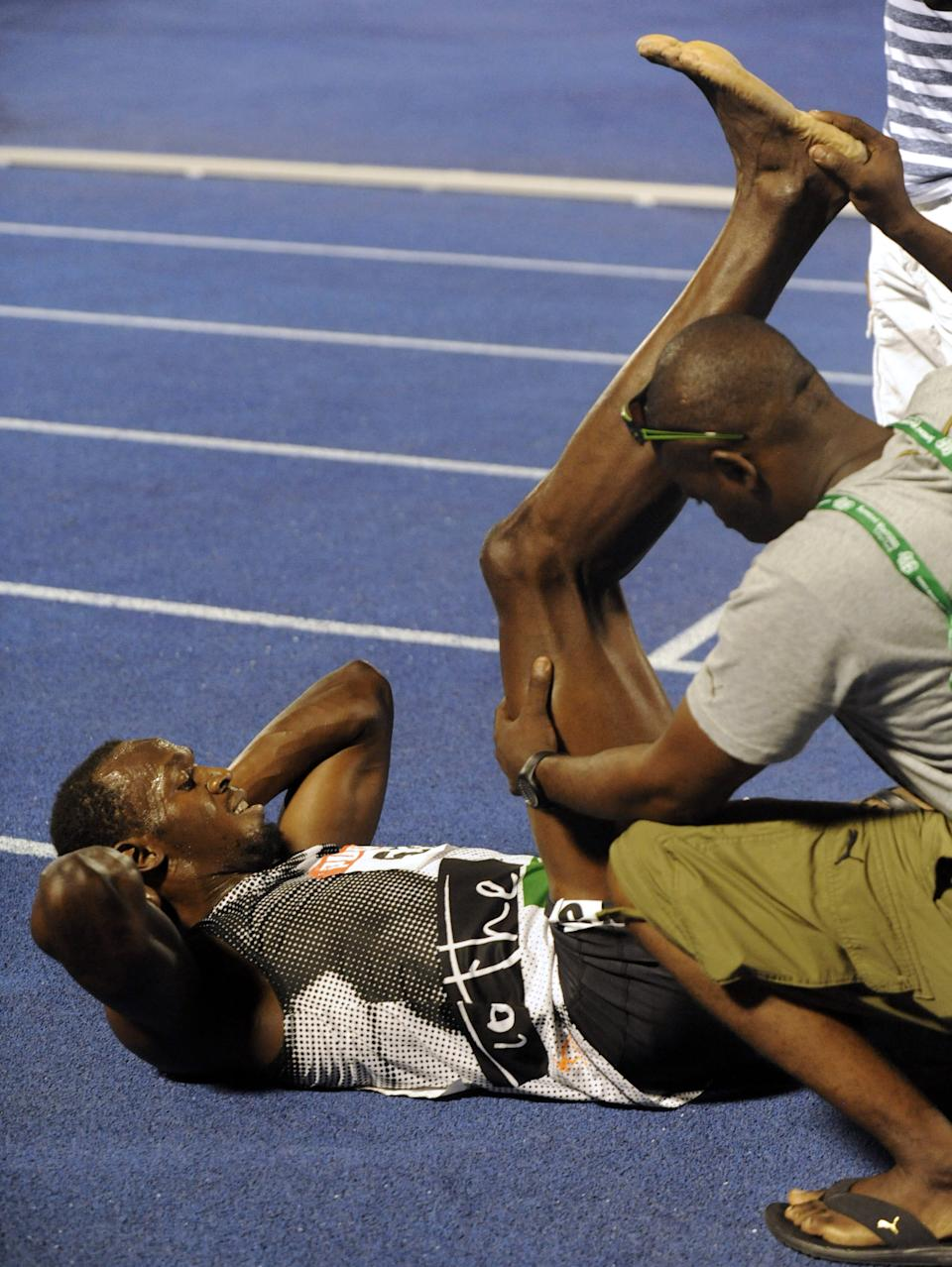 World-record holder Usain Bolt gets his right hamstring stretched out after loosing to fellow country man Yohan Blake in the 200m final at Jamaica's Olympic trials in Kingston, Jamaica, Sunday, July 1, 2012.  Blake edged Bolt by 0.03 finishing in 19.80 seconds. (AP Photo/Collin Reid)