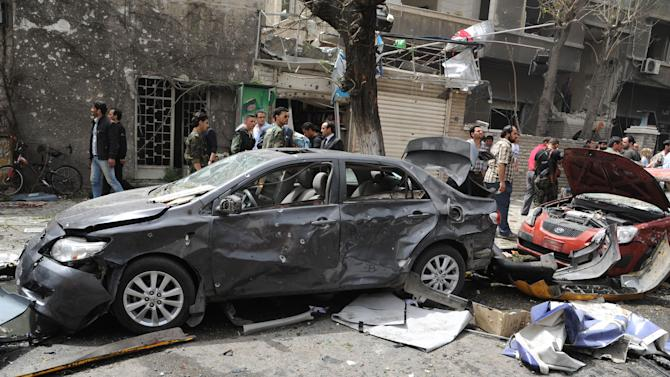 This photo released by the Syrian official news agency SANA, shows Syrians inspecting a damaged car at the scene of a car bomb attack near the Sabaa Bahrat Square, one of the capital's biggest roundabouts, in Damascus, Syria, Monday, April. 8, 2013. A car bomb rocked a busy residential and commercial district in central Damascus on Monday, killing more than a dozen with many more injured and sending a huge cloud of black smoke billowing over the capital's skyline, Syrian state-run media said. (AP Photo/SANA)
