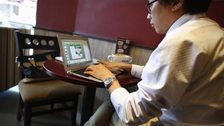 A man works on his computer inside a coffee shop in downtown Shanghai