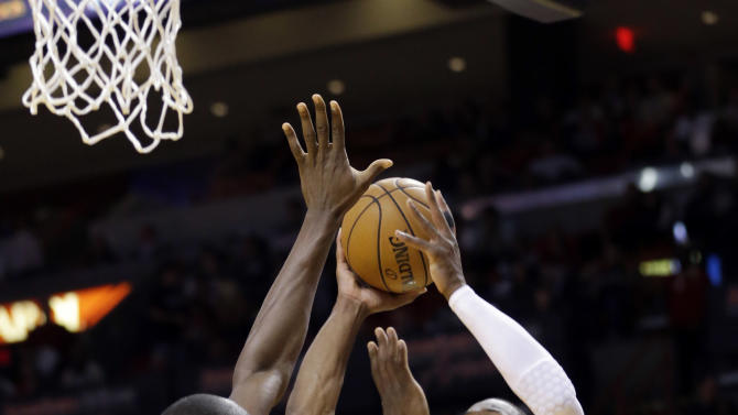 Miami Heat guard Dwyane Wade (3) goes up for a shot against Charlotte Bobcats forward Bismack Biyombo of the Democratic Republic of Congo, during the first half of an NBA basketball game, Monday, Feb. 4, 2013 in Miami. (AP Photo/Wilfredo Lee)