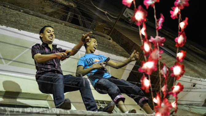 In this Tuesday, April 16, 2013 photo, young Egyptian men dance with pistols at a wedding party in Cairo, Egypt. Egypt's economy has been hard hit by the two years of turmoil that followed the ouster of longtime President Hosni Mubarak. Half of the country's 85 million people live at or below the poverty line of $2 a day and rely on government subsidies of wheat and fuel for survival.(AP Photo/Eman Helal)