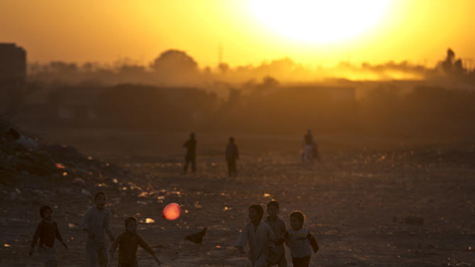 Afghan refugees and internally displaced Pakistani children chase a red balloon while playing in a field as the sun sets on the outskirts of Islamabad, Pakistan, Friday, Dec. 26, 2014. (AP Photo/Muhammed Muheisen)