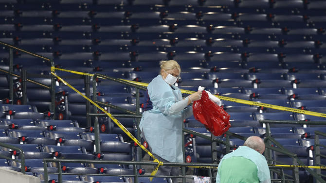 People clean a section of the lower seating area at Turner Field where a fan fell from the upper deck during a baseball game between the Atlanta Braves and the New York Yankees, Saturday, Aug. 29, 2015, in Atlanta. The fan was pronounced dead at Grady Memorial Hospital, authorities said. (AP Photo/John Bazemore)