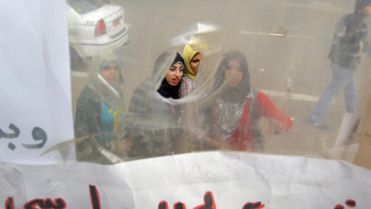 "Egyptians read slogans on a poster displayed in a temporary exhibit of revolutionary paraphernalia in Tahrir Square in Cairo, Egypt, Sunday, Dec. 30, 2012. Arabic reads, "" Morsi, you don't have any legality."" (AP Photo/Amr Nabil)"