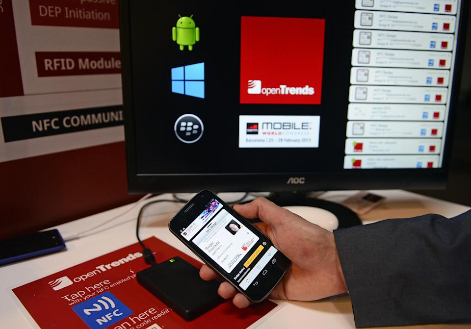FILE - In this Feb. 27, 2013 file photo, a man uses the NFC communicate library system at the Mobile World Congress, the world's largest mobile phone trade show, in Barcelona, Spain.  (AP Photo/Manu Fernandez)