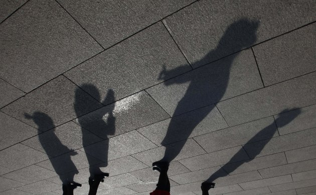 Shadows of hostesses are cast on the ground as they take pictures on Tiananmen Square before the opening ceremony of CPPCC in Beijing