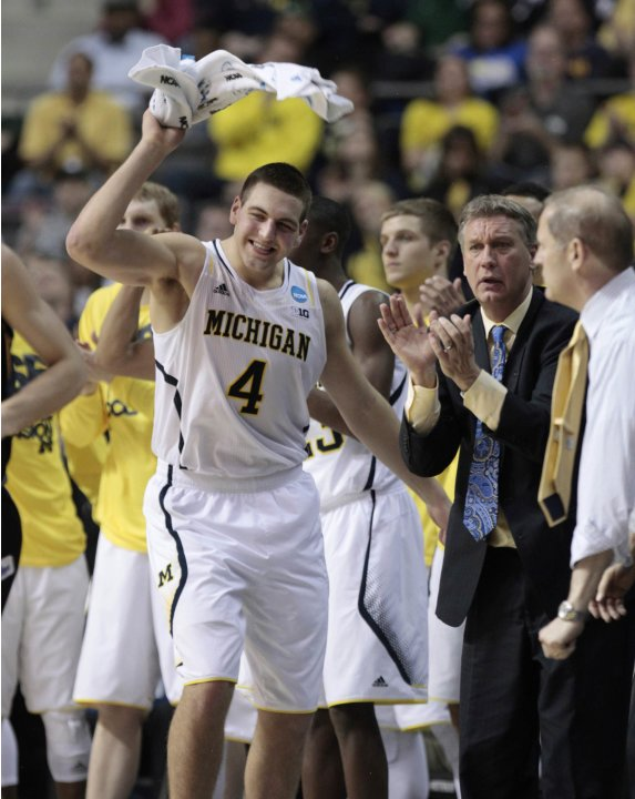 Michigan Wolverines' McGary celebrates on the bench during their NCAA basketball game against South Dakota State in Auburn Hills