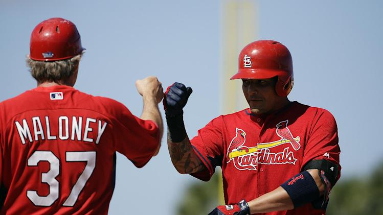 St. Louis Cardinals' Yadier Molina, right, fist-bumps first base coach Chris Maloney, left, after hitting a single in the fourth inning of an exhibition spring training baseball game against the Washington Nationals, Saturday, March 8, 2014, in Jupiter, Fla