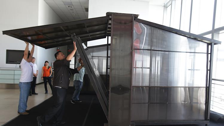 "In this March 12 photo, Filipino-American Rogelio Santos Jr., center, and workers demonstrate how to assemble the panels of the ""Butterfly house"" that is on display at a convention center in suburban Pasay, south of Manila, Philippines. Santos invented the quick-construct house in response to the lack of housing in communities affected by typhoon Haiyan which displaced 4.1 million Filipinos in central Philippines last November 8, 2013. The 11.5-square-meter Butterfly house cost about 50,000 pesos per unit (about US $1,120). (AP Photo/Aaron Favila)"