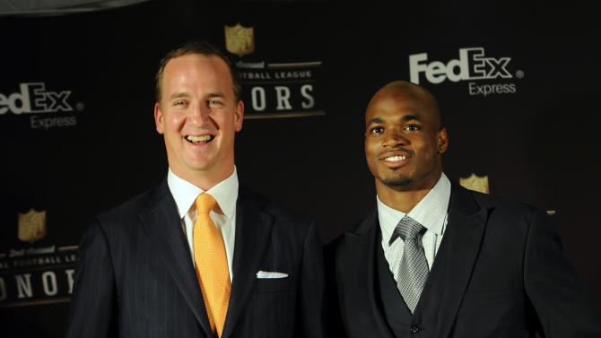 Denver Broncos quarterback Peyton Manning and Minnesota Vikings running back Adrian Peterson accept the FEDEX Air and Ground NFL Players of the Year Award at the NFL Honors on Saturday, Feb. 2, 2013 in New Orleans. (Photo by Cheryl Gerber/Invision/AP Images)