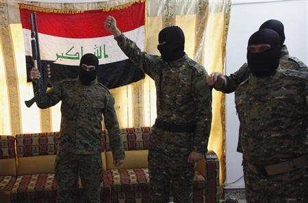 Fighters from Iraq's Islamist Shi'ite militias celebrate before departing to Syria from Baghdad