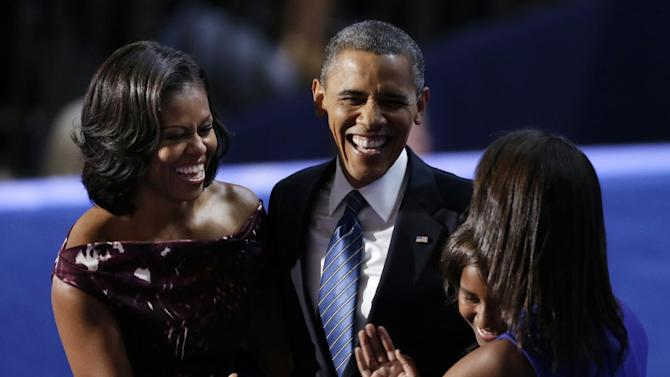 """FILE - In this Sept. 6, 2012 file photo, President Barack Obama laughs with his wife Michelle and his daughters Malia and Sasha after his speech to the Democratic National Convention in Charlotte, N.C.  Call it the campaign trail schtick. Have you heard the one about the kid who thinks President Barack Obama's job is to """"approve this message?"""" Or the time Mitt Romney compared another presidential run to giving birth? The jokes at presidential fundraisers and rallies are easy applause lines for Obama and Romney, a way to keep supporters entertained before more weighty subjects like Medicare, taxes and foreign policy. A good sense of humor has served presidential candidates well in the past. So it's little wonder why both Obama and Romney are using the same technique.  (AP Photo/Lynne Sladky, File )"""
