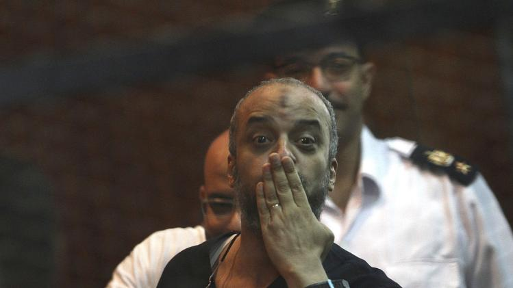 Mohamed El-Beltagi, a leading figure of the Muslim Brotherhood, gestures during his trial at a court in Cairo