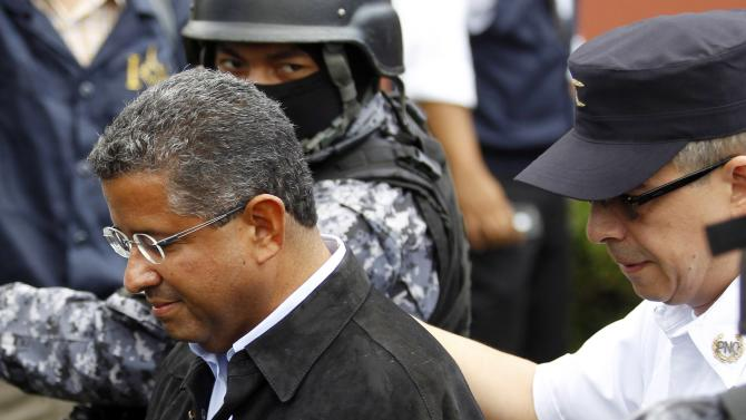 Former El Salvador President Flores walks out of his house as he is guarded by Deputy Director of Police Cotto in San Benito