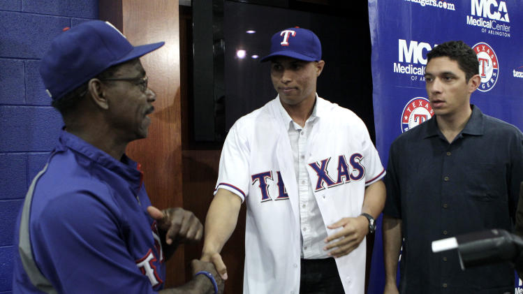 Texas Rangers manager Ron Washington shakes hands with newly-signed baseball player Leonys Martin, center, as team general manager Jon Daniels, right, looks on following a news conference, Wednesday, May 11, 2011, in Arlington, Texas. (AP Photo/Tony Gutierrez)