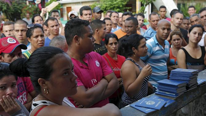 Cuban migrants wait to receive their passports from the migration office in Puerto Obaldia