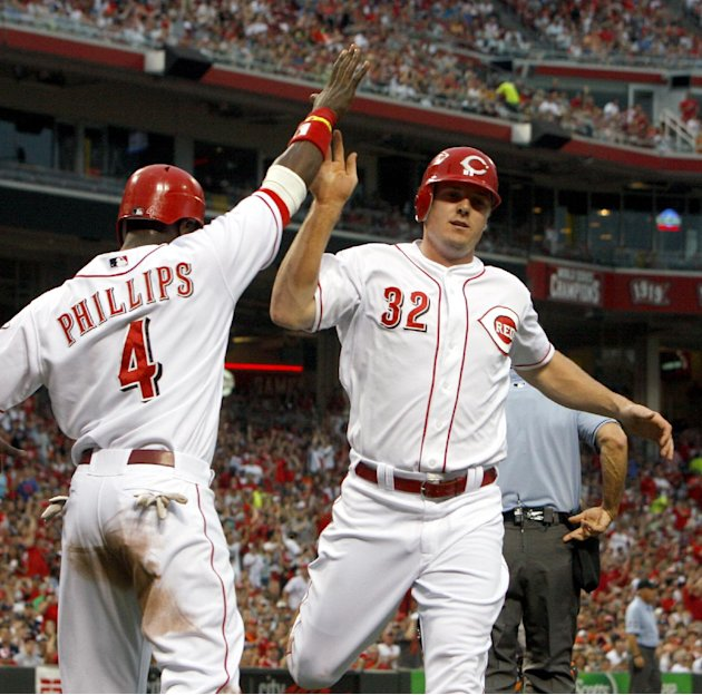Cincinnati Reds' Jay Bruce (32) is congratulated by Brandon Phillips (4) after they scored on a single hit by Todd Frazier off Detroit Tigers starting pitcher Drew Smyly in the second inning of a base
