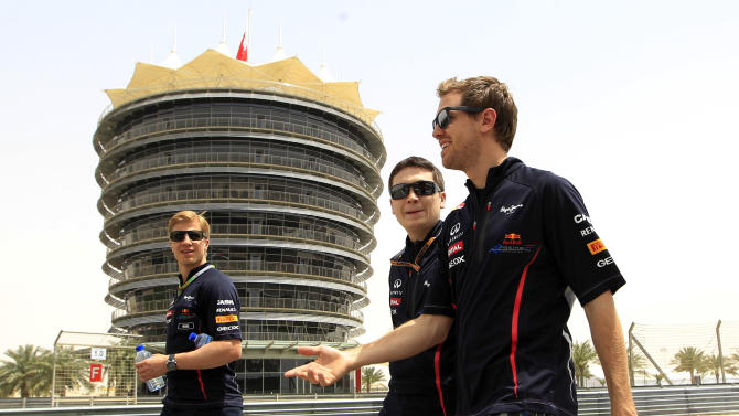Red Bull driver Sebastian Vettel of Germany, right, walks with team technicians at the Formula One Bahrain International Circuit in Sakhir, Bahrain, Thursday, April 19, 2012. The Bahrain Grand Prix was canceled last year due to anti-government protests that have left nearly 50 dead, but last week Formula One boss Bernie Ecclestone declared the Gulf kingdom safe and decided to go ahead with this year's race. The Bahrain Formula One Grand Prix will take place here on Sunday. (AP Photo/Luca Bruno)