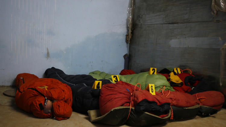 Bodies of climbers killed in an avalanche at Mount Manaslu lie covered with numbers at the Tribhuvan University Teaching hospital in Katmandu, Nepal, Monday, Sept. 24, 2012. Rescue helicopters flew over the high slopes of a northern Nepal peak again Monday to search for climbers lost in an avalanche that killed at least nine mountaineers and injured others. Many of the climbers were French, German and Italian. (AP Photo/Niranjan Shrestha)