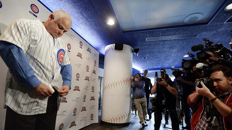 Chicago Cubs' new manager Rick Renteria puts on his jersey during a baseball press conference at Wrigley Field in Chicago, Thursday, Dec., 5, 2013. Renteria met with the media for the first time since he was hired last month, while recuperating in San Diego from hip surgery
