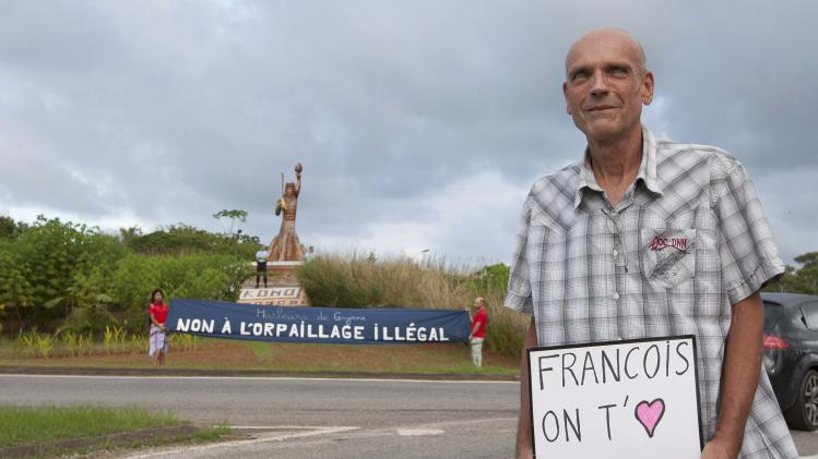 A man holds a sign in support of French President Hollande in Cayenne