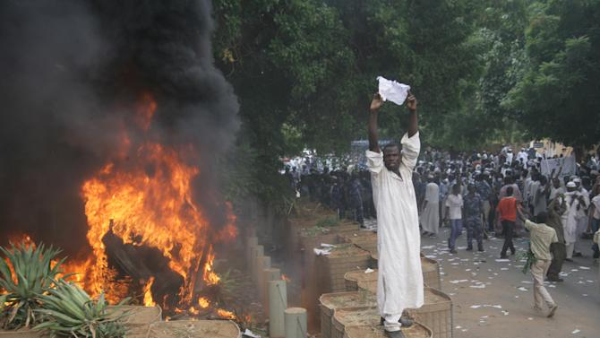 A Sudanese protester stands on a barricade during a demonstration in Khartoum, Sudan, Friday, Sept. 14, 2012, as part of widespread anger across the Muslim world about a film ridiculing Islam's Prophet Muhammad. Germany's Foreign Minister says the country's embassy in the Sudanese capital of Khartoum has been stormed by protesters and set partially on fire. Minister Guido Westerwelle told reporters that the demonstrators are apparently protesting against an anti-Islam film produced in the United States that denigrates the Prophet Muhammad.(AP Photo/Abd Raouf)