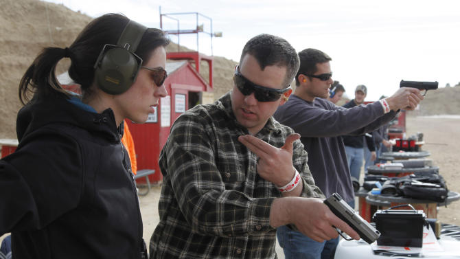In this Saturday Dec. 22, 2012 photo, U.S. Army 1st Lt. Aaron Dunn, center, instructs his wife Leanne in effective hand gun operation, at Dragonman's firing range and gun dealer, outside Colorado Springs, Colo. 1st Lt. Dunn returned from a deployment in the mountains of Afghanistan on Nov. 30, 2012. (AP Photo/Brennan Linsley)