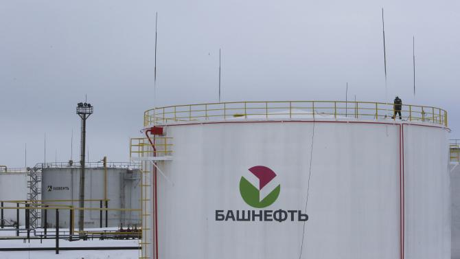 A worker walks on the top of a storage tank at an oil gathering facility owned by Bashneft company near Shushnur