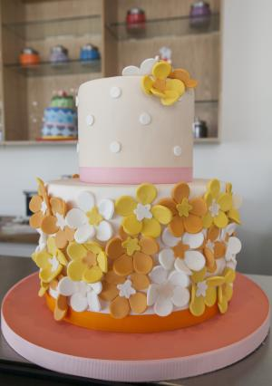 This image taken on Wednesday, June 20, 2012, shows a two-tier cake that is fondant covered and made with fondant cut-out flowers, to serve as inspiration for customers creating a make-your-own cake at Duff's Cakemix, in Los Angeles. The new venture is owned by chef, Duff Goldman, next door to his bakery, Charm City Cakes West.  (AP Photo/Damian Dovarganes)