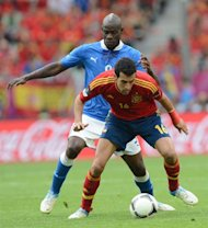 Italian forward Mario Balotelli (L) vies with Spanish midfielder Sergio Busquets during the Euro 2012 championships football match Spain vs Italy on June 10, 2012 at the Gdansk Arena. AFP PHOTO / CHRISTOF STACHE