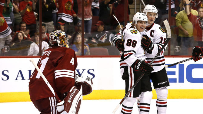 Chicago Blackhawks' Patrick Kane (88) celebrates his goal against Phoenix Coyotes' Mike Smith, left, his second of the period, with teammate Jonathan Toews (19) during the first period in an NHL hockey game Thursday, Feb. 7, 2013, in Glendale, Ariz.(AP Photo/Ross D. Franklin)