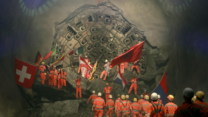 Miners wave with the flags of their home countries as they celebrate as fireworks explode after a giant drill machine broke through the rock at the final section Sedrun-Faido, at the construction site of the NEAT Gotthard Base Tunnel