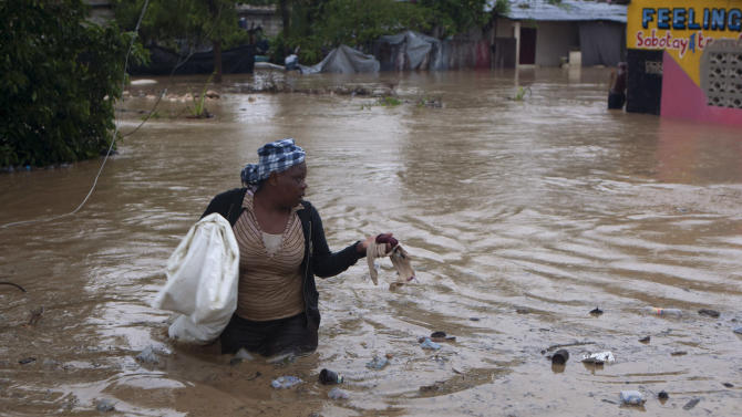 A woman wades through a flooded street triggered by Tropical Storm Isaac in Port-au-Prince, Haiti, Saturday, Aug. 25, 2012. Tropical Storm Isaac swept across Haiti's southern peninsula early Saturday, dousing a capital city prone to flooding and adding to the misery of a poor nation still trying to recover from the 2010 earthquake. (AP Photo/Dieu Nalio Chery)