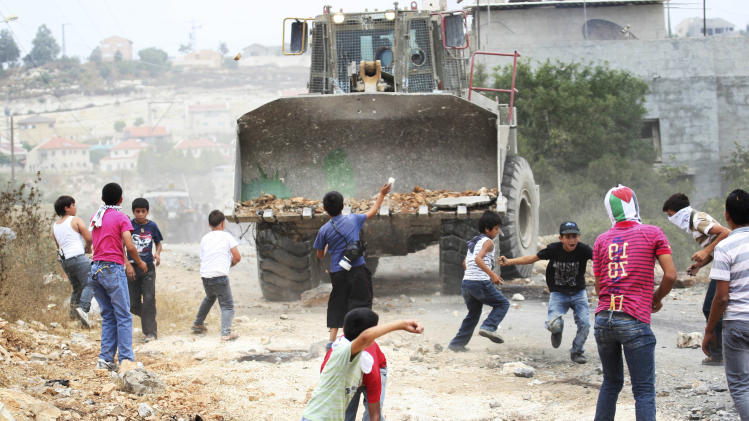 Palestinian youths throw stones at an Israeli military bulldozer during a protest against the expansion of the nearby Jewish settlement of Kdumim, in the northern West Bank village of Kufr Qaddum, Friday, June 22, 2012. (AP Photo/Nasser Ishtayeh)