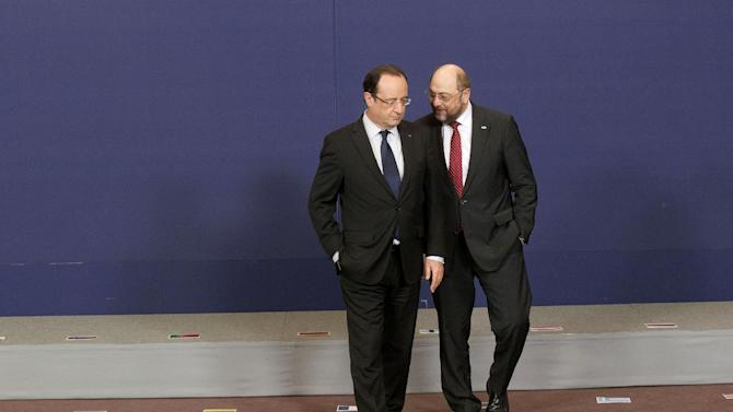 France's President Francois Hollande, left, and President of the European Parliament, Martin Schulz, right, talk together after a group photo at a EU Budget summit at the European Council building in Brussels, Thursday, Feb. 7, 2013. European Union leaders drew hard lines Thursday ahead of a struggle over EU spending for the next seven years that reflects deep divisions about the role of their union. (AP Photo/Michel Euler)