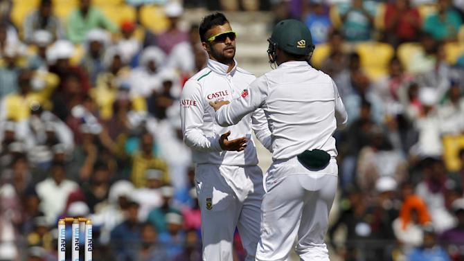 South Africa's Duminy is congratulated by his team mate Elgar after taking the wicket of India's Pujara during the second day of their third test cricket match in Nagpur